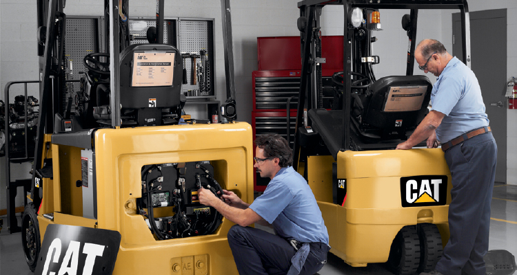 Two workers repairing the backs of different Cat forklifts