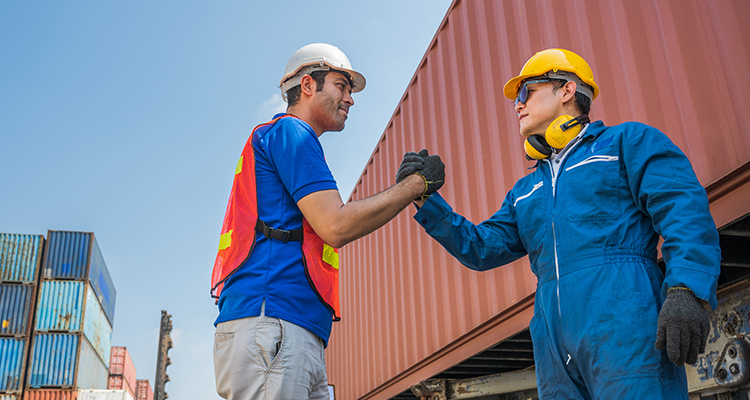 two co-workers shaking hands near shipping container