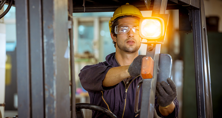 Man installing flashing amber light on forklift