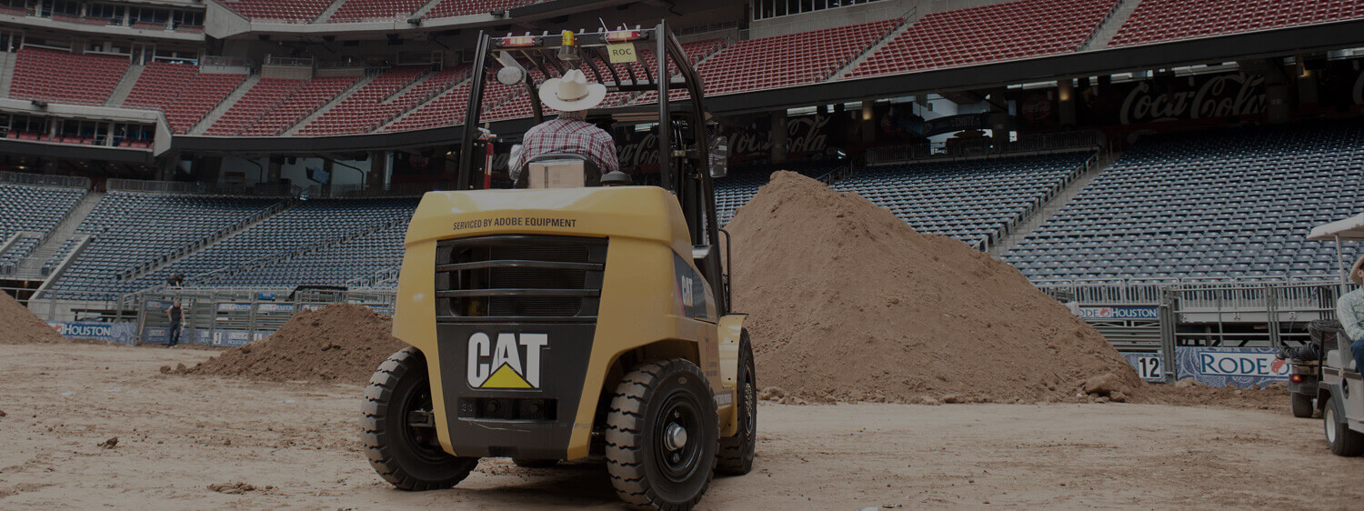 Man Wearing a Cowboy Hat Driving a CAT Forklift in the Rodeo Stadium