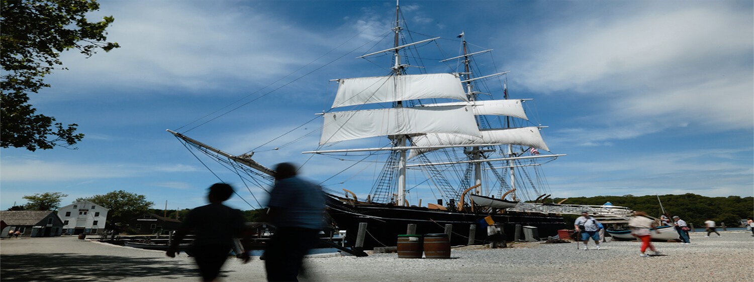 Old-fashioned whale ship with white sails docked at port with people walking around