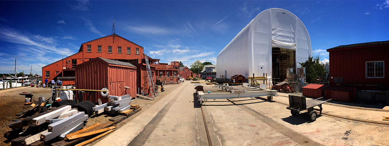 Mystic seaport worksite with warehouses, tents and ship materials