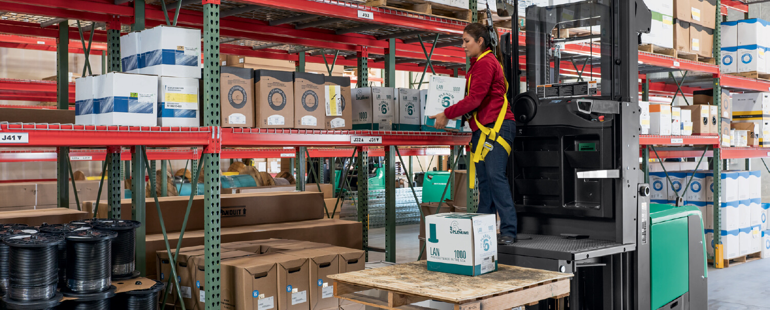 Woman on Mitsubishi order picker lifting box from racking