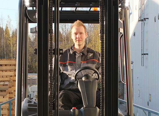 Man Smiling at the Camera While Sitting in a Mitsubishi Forklift