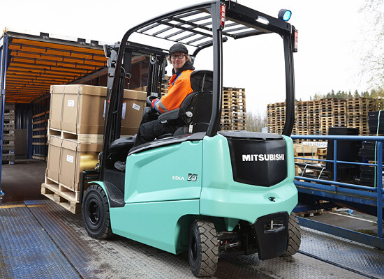 Worker backing out of a loading truck driving a Mitsubishi forklift