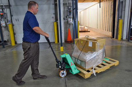 Man pulling Mitsubishi hand pallet truck loaded with boxes