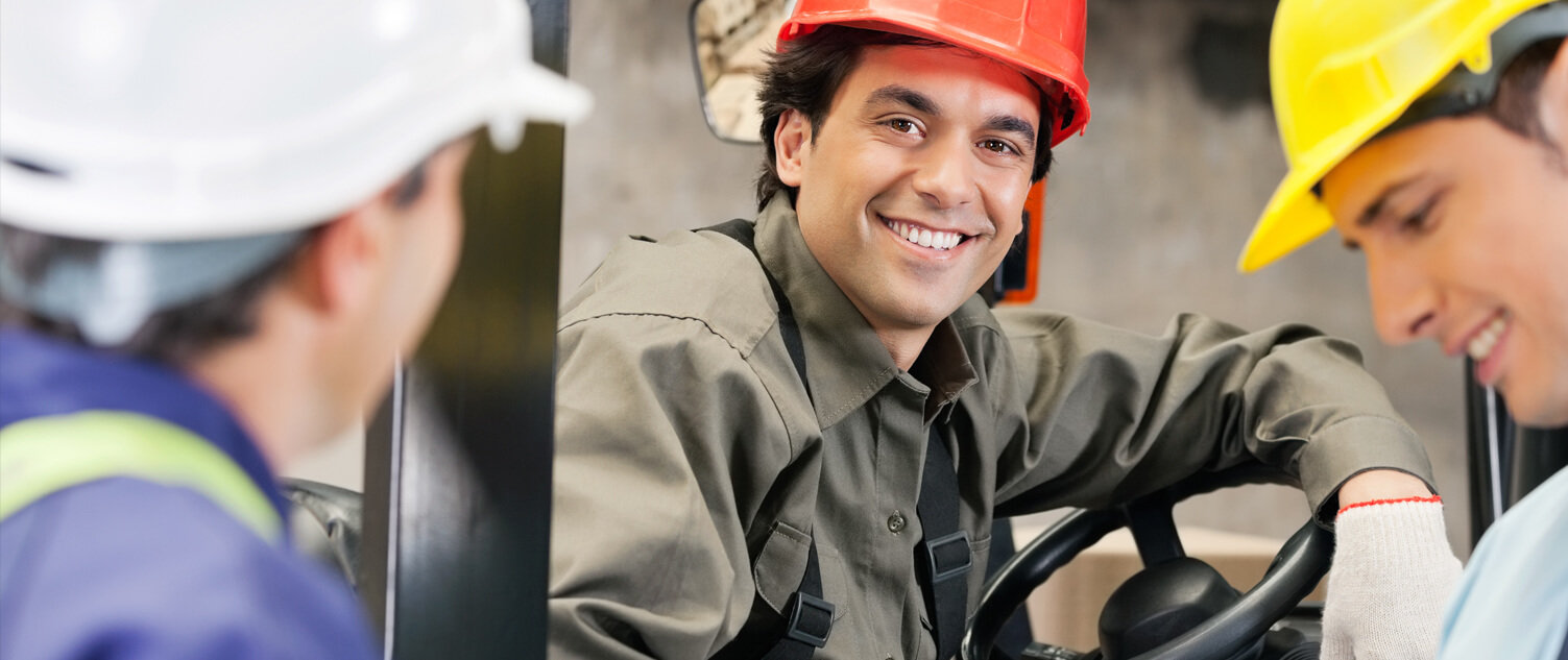 Man Smiling and Sitting in a Forklift